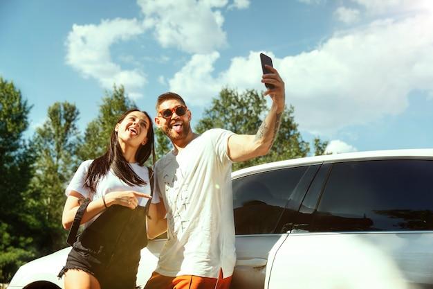 Młoda para jedzie na wakacje w samochodzie w słoneczny letni dzień. kobieta i mężczyzna robi selfie w lesie i wygląda na szczęśliwego. pojęcie związku, wakacje, lato, wakacje, weekend, miesiąc miodowy.