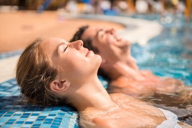 Młoda para jest relaks w basenie.
