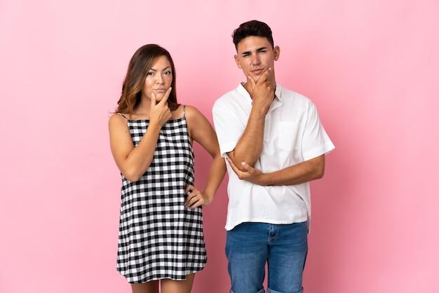 Młoda para kaukaska na różowo ma wątpliwości i zmieszany wyraz twarzy