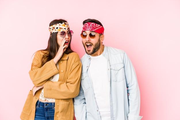 Młoda para kaukaska ubrana w stroje z festiwalu muzycznego na białym tle mówi tajną wiadomość o hamowaniu i spogląda na bok