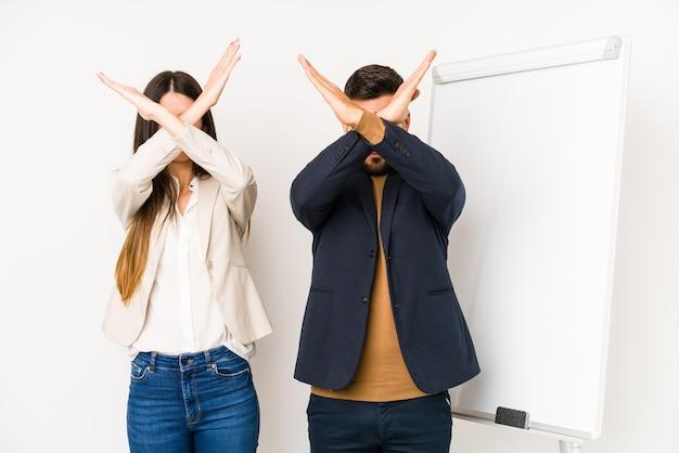 Młoda para kaukaski biznes na białym tle trzymając dwie skrzyżowane ręce, koncepcja odmowy.