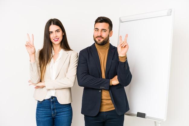 Młoda para kaukaski biznes na białym tle wyświetlono numer dwa palcami.
