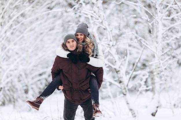 Młoda para kaukaski mężczyzna i kobieta jedzie na plecach na ferie zimowe w zaśnieżonym lesie