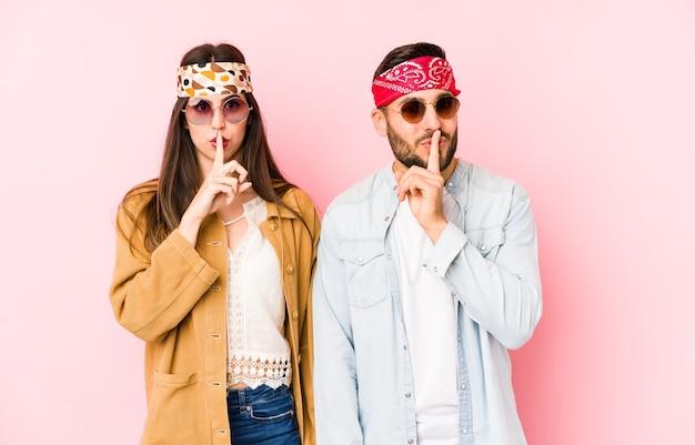 Młoda para kaukaski w strojach festiwalu muzycznego na białym tle, zachowując tajemnicę lub prosząc o ciszę.