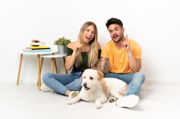 Młoda para kaukaski z psem przebywa w domu myśląc na pomysł wskazując palcem w górę
