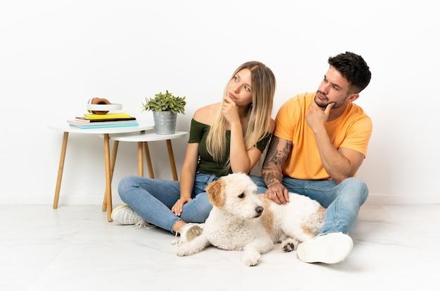 Młoda para kaukaski z psem przebywa w domu, patrząc z boku