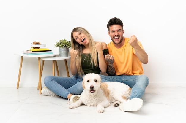 Młoda para kaukaski z psem w domu świętuje zwycięstwo na pozycji zwycięzcy