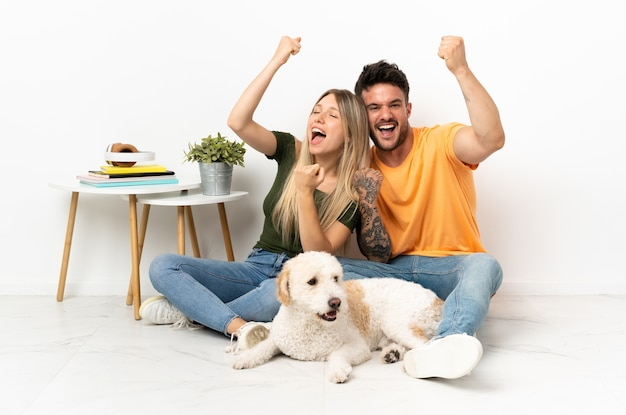 Młoda para kaukaski z psem w domu świętuje zwycięstwo