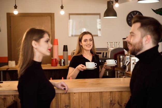 Młoda para klientów biorących kawę od baristy w kawiarni.