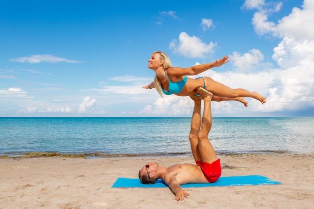 Młoda para kobieta i mężczyźni na plaży razem robić ćwiczenia jogi fitness. element acroyoga dla siły i równowagi