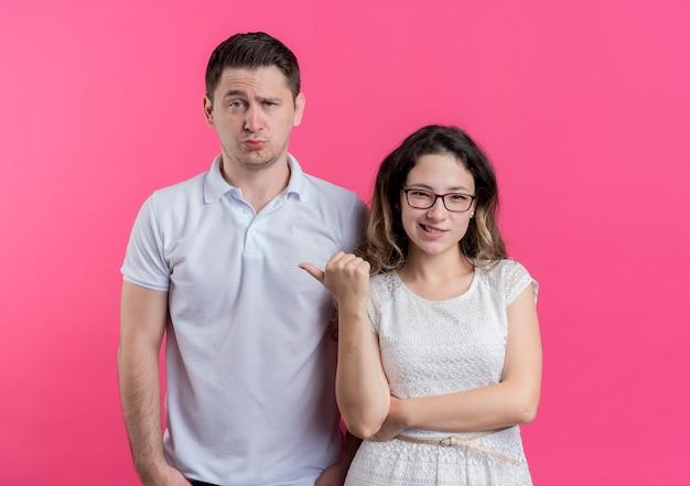 Młoda para kobieta, wskazując palcem na swojego zmieszanego chłopaka stojącego na różowej ścianie