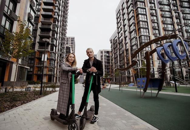 Młoda para kocha nowoczesne technologie. atrakcyjna blondynka i przystojny mężczyzna w eleganckich ciuchach spędzają razem czas na skuterach elektrycznych. ekologiczny styl życia.