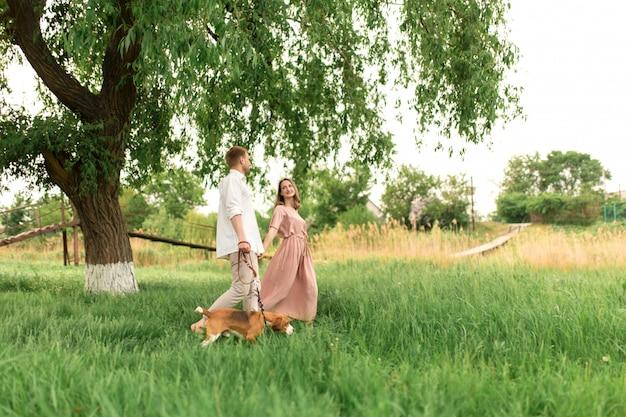 Młoda para kochająca zabawę i bieganie po zielonej trawie na trawniku ze swoim ukochanym domowym psem rasy beagle i bukietem kwiatów