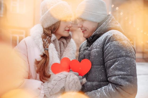 Młoda para kochających się na zewnątrz w zimowy dzień, trzymając w rękach czerwone papierowe serca, czując radość i miłość. romantyczny mężczyzna i kobieta świętują walentynki pod śniegiem w parku.