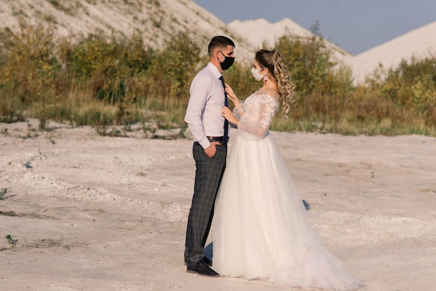 Młoda para kochających spacery w maskach medycznych w parku podczas kwarantanny w dniu ślubu.