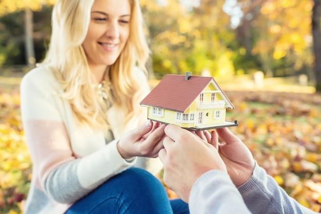 Młoda para kochających trzymając mały model domu w jesiennym ogrodzie lub parku.