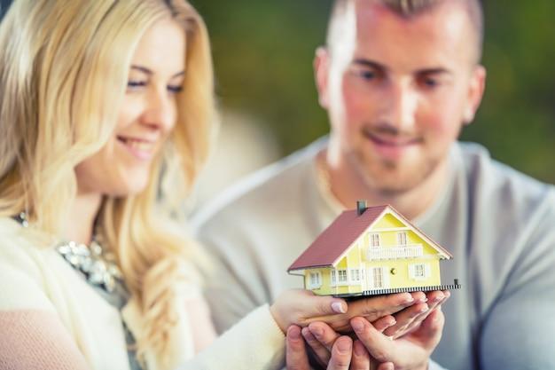 Młoda para kochających trzymając mały model domu.