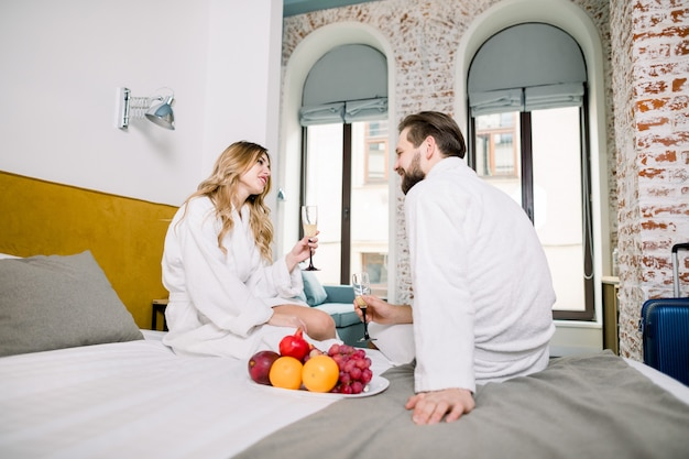 Młoda para kochanków w białych szlafrokach hotelowych jeść świeże owoce i pić szampana w łóżku