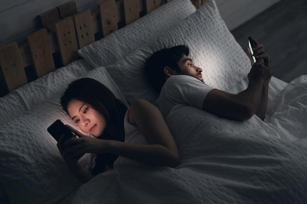 Młoda para konfliktu w łóżku. szczęśliwa uśmiechnięta kobieta odwróciła się plecami do mężczyzny, czytając wiadomość w telefonie komórkowym, próbując zerknąć na ekran