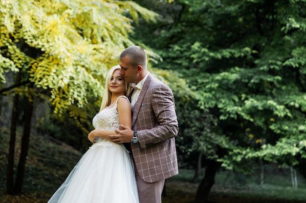 Młoda para korzystających z romantycznych chwil podczas spaceru w parku. stylowy narzeczeni pozowanie i całując w parku w dniu ślubu. elegancka panna młoda w pięknej białej sukni, pan młody w garniturze.