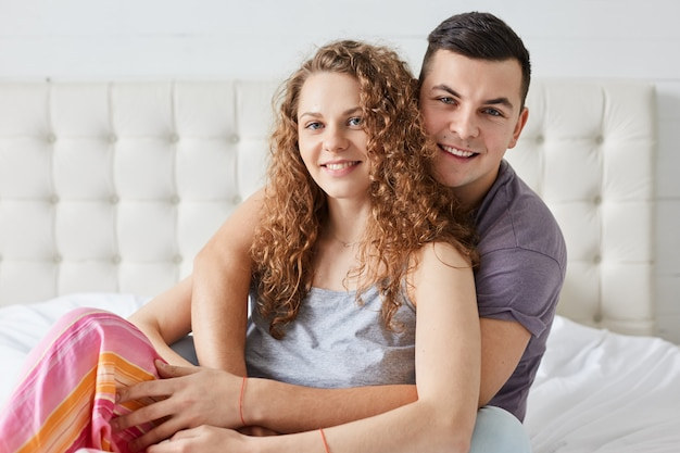 Młoda para, kręcone włosy wonan i przyzwyczajony mężczyzna, siedzą w łóżku, obejmują się i rozmawiają, patrząc bezpośrednio w kamerę, mają wyraz twarzy. romantyczna para zakochanych