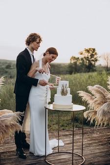 Młoda para kroi tort weselny
