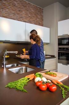 Młoda para kroi warzywa w kuchni, aby przygotować jedzenie