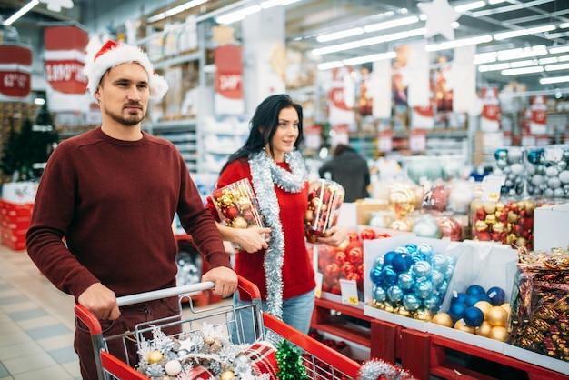 Młoda para kupuje dużo ozdób choinkowych w supermarkecie