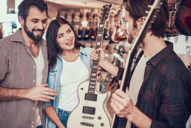 Młoda para kupuje nową gitarę elektryczną, konsultując się ze sprzedawcą w sklepie muzycznym.