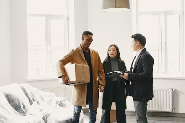 Młoda para kupuje nowy dom. azjatycka kobieta i afrykanin. podpisywanie dokumentów w nowym domu.