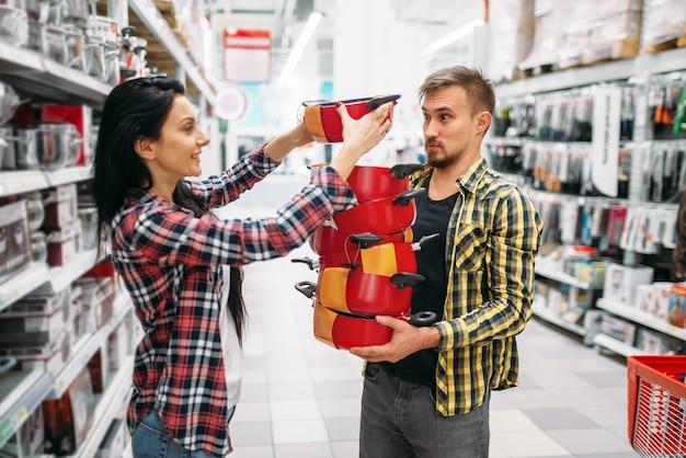 Młoda para kupuje patelnie w supermarkecie. klienci płci męskiej i żeńskiej na rodzinne zakupy. mężczyzna i kobieta kupują towary do domu