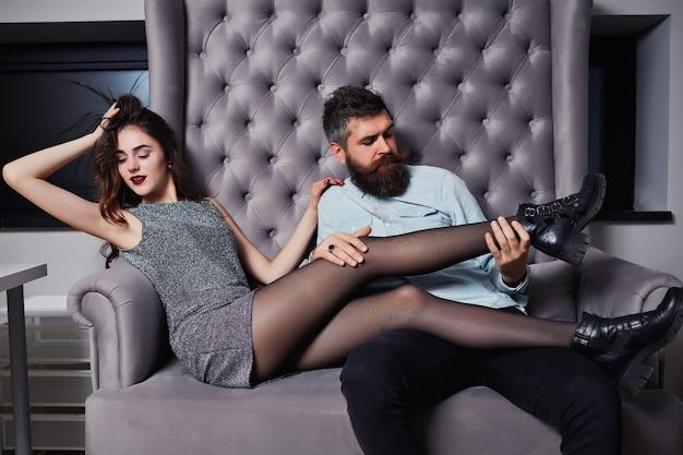 Młoda para ładna kobieta w szarej sukience i przystojny mężczyzna z długą brodą w koszuli.
