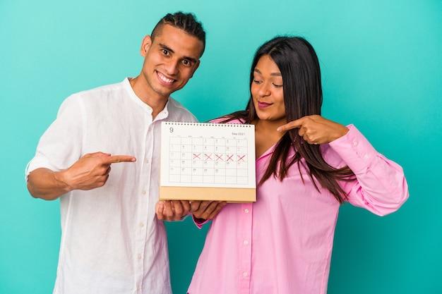 Młoda para latynoska trzymająca kalendarz na białym tle na niebieskiej ścianie