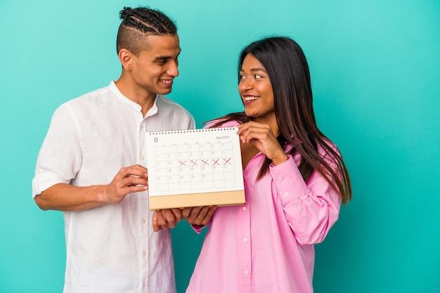 Młoda para latynoska trzymająca kalendarz na białym tle na niebieskim tle
