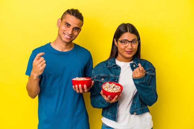 Młoda para latynoska trzymająca miskę płatków śniadaniowych na żółtej ścianie, wskazując palcem na ciebie, jakby zapraszając do siebie.