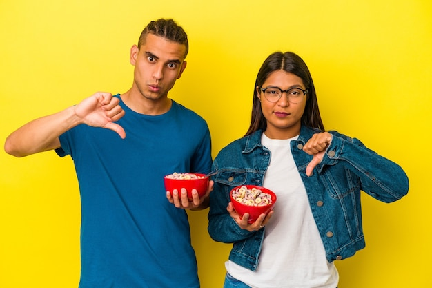 Młoda para latynoska trzymająca miskę zbóż na białym tle na żółtym tle pokazujący gest niechęci, kciuk w dół. koncepcja niezgody.