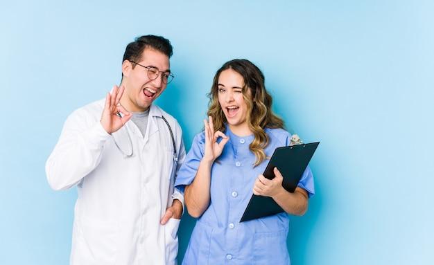 Młoda para lekarz pozuje w niebieskiej ścianie na białym tle mruga okiem i trzyma w porządku gest ręką.
