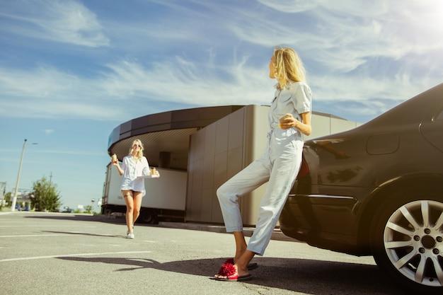 Młoda para lesbijek przygotowuje się do wakacyjnej podróży samochodem w słoneczny dzień