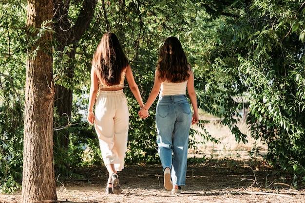 Młoda para lesbijek, trzymając się za ręce, spacery o zachodzie słońca