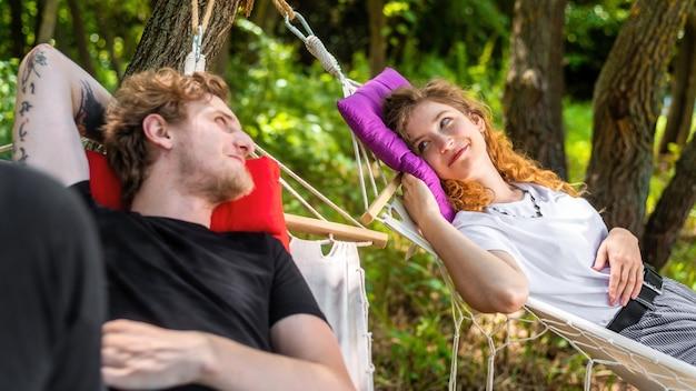 Młoda para leżąc na hamakach, patrząc na siebie i uśmiechając się. wokół zieleń. glamping