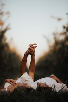 Młoda para, leżąc na trawie, trzymając się za ręce i patrząc na siebie.