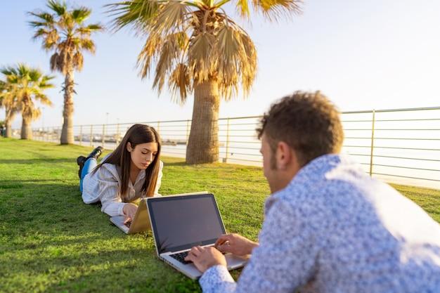Młoda para, leżąc na trawie w inteligentny pracy z laptopem naprzeciw siebie o zachodzie słońca lub świcie.