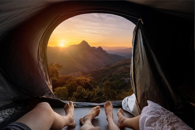 Młoda para, leżąc w namiocie kempingowym i patrząc na zachód słońca nad górą