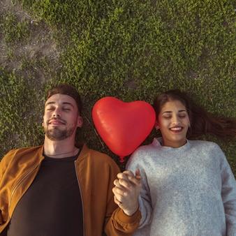 Młoda para leżącego na trawie z balonem serca