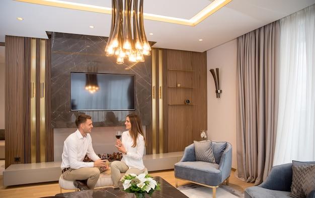 Młoda para ma romantyczny wieczór przy lampce czerwonego wina w domu we współczesnym salonie