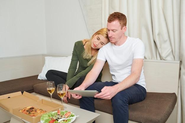 Młoda para ma sałatkę z pizzy i białe wino na kolację i ogląda film na komputerze typu tablet