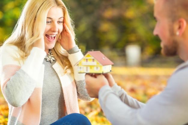 Młoda para małżeńska mąż zaskakuje żonę małżonkę nowym domem rodzinnym szczęśliwym kredytem hipotecznym.