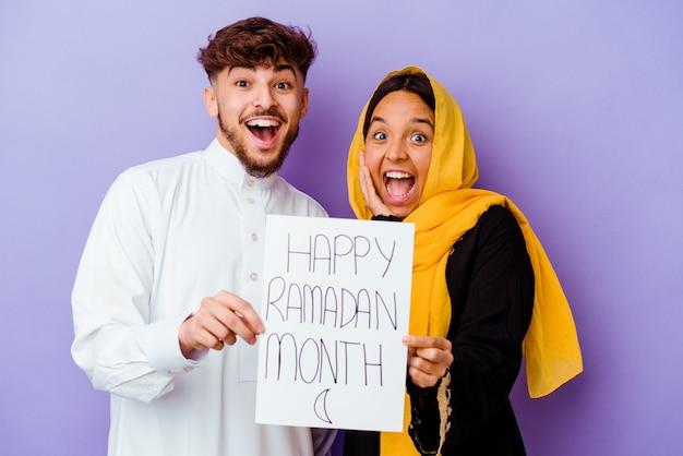 Młoda para marokańskich ubrana w typowy strój arabski obchodzi ramadan na białym tle na fioletowym tle