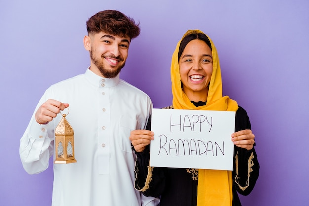 Młoda para marokańskich ubrana w typowy strój arabski świętuje ramadan na fioletowym tle