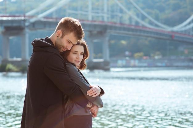 Młoda para mężczyzna i kobieta biegnący na świeżym powietrzu nad rzeką na tle mostu